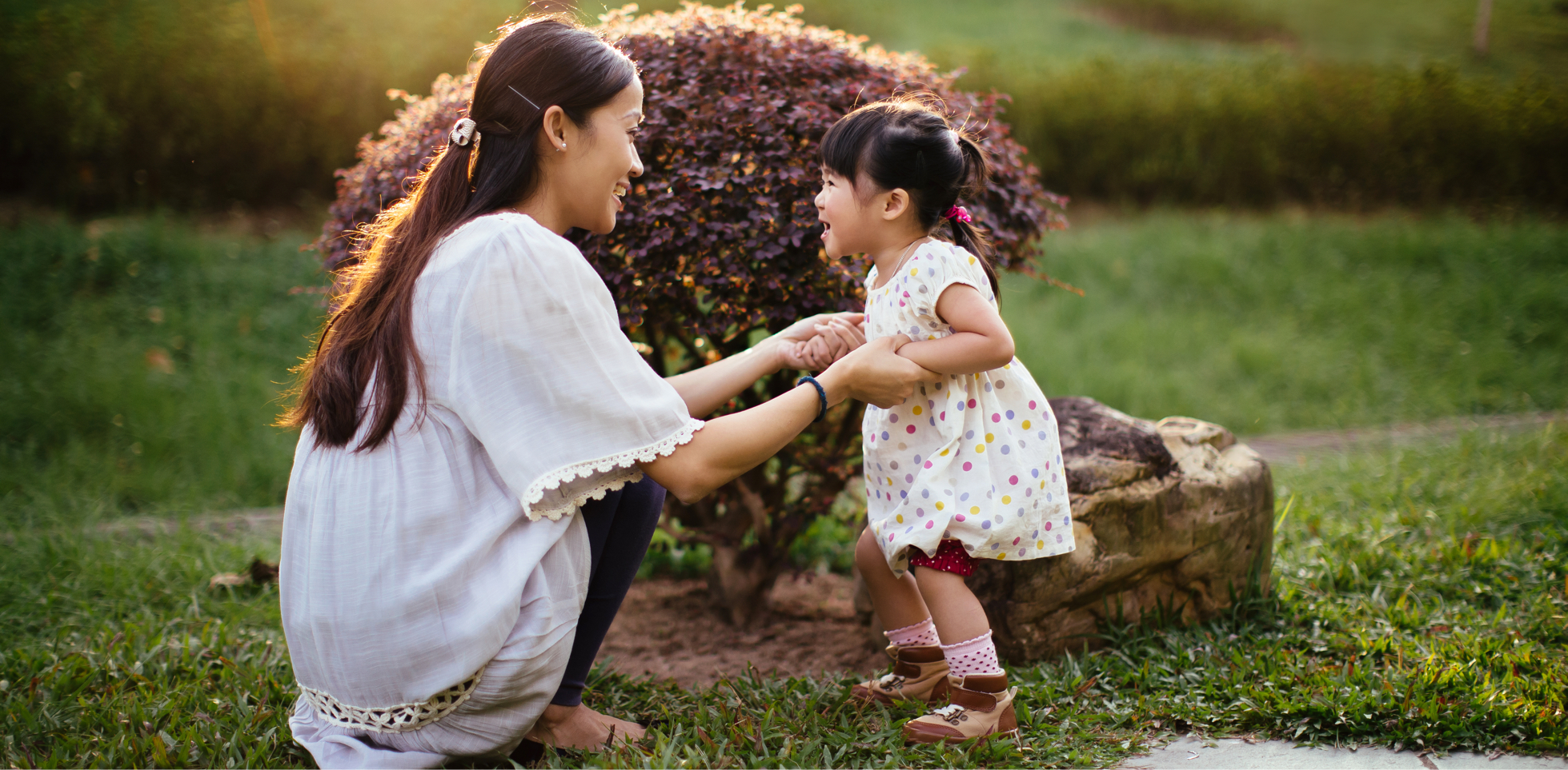 Mother and small child playing in garden